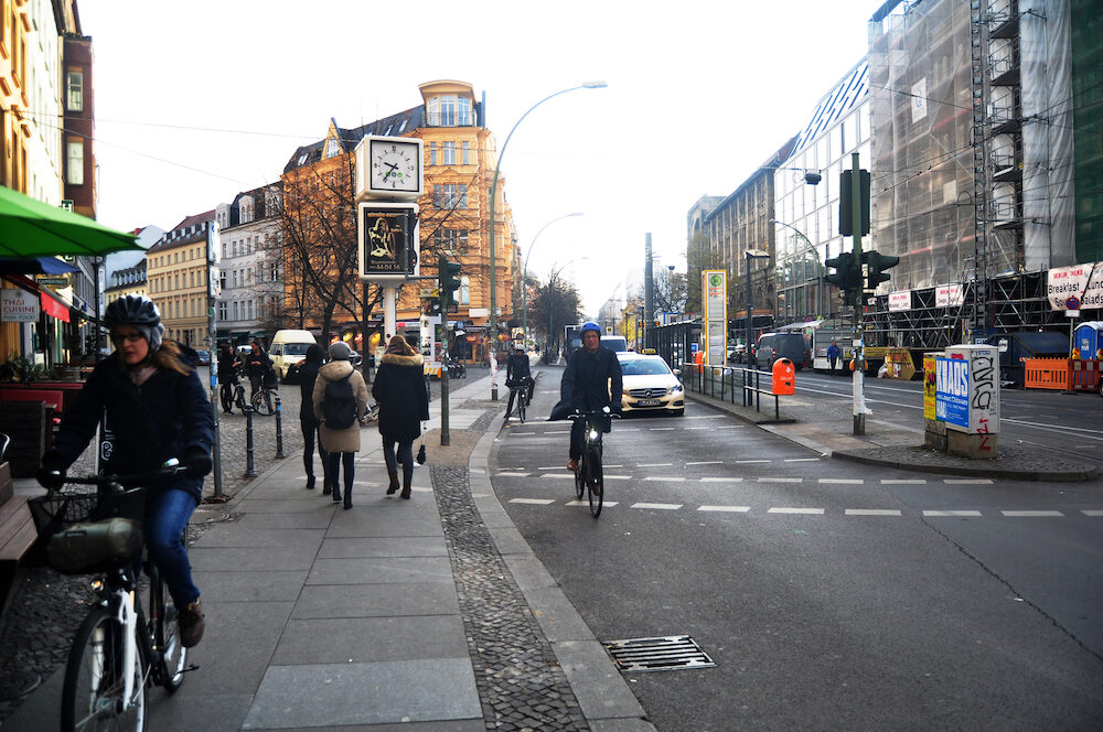 View cityscape of German people walking on the footpath and biking bicycle with Traffic road and classic building