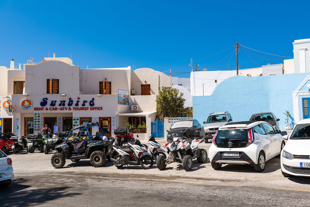 SANTORINI, GREECE - : Parked rental cars and quadricycles are staying near rental office at Imerovigli town.