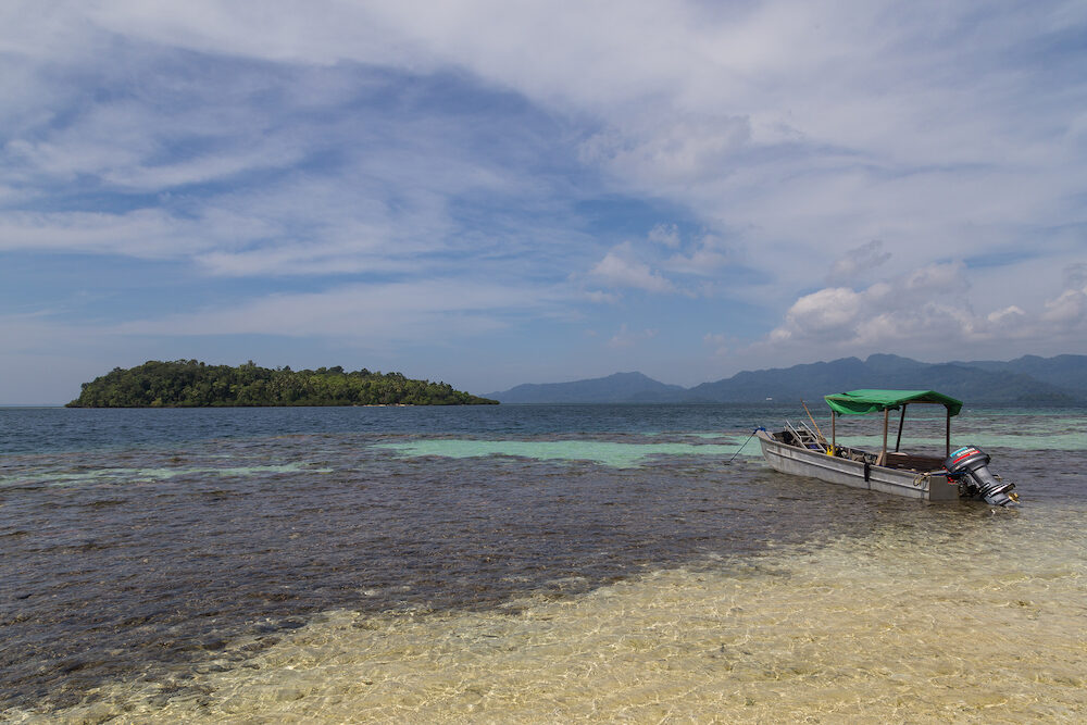 Marovo Lagoon, Solomon Islands - A small diving boat anchored in front of a small island