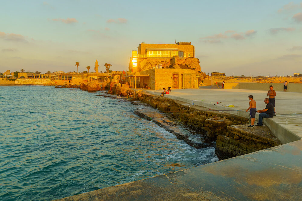 Caesarea, Israel - Sunset view of the old port, with fishermen and other visitors, in Caesarea National Park, Northern Israel