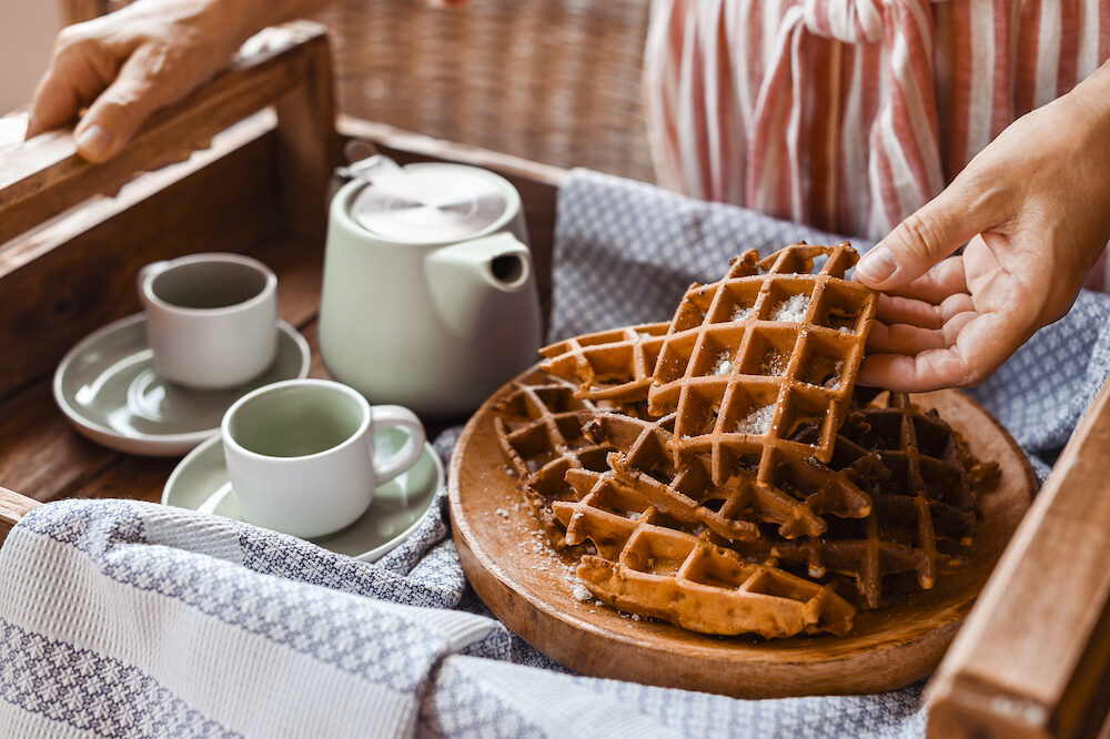 Women holds fresh baked waffles and tea mugs for breakfast. Morning coffee with homemade cakes. Toned photo. Cozy atmosphere at home and flowers on the table