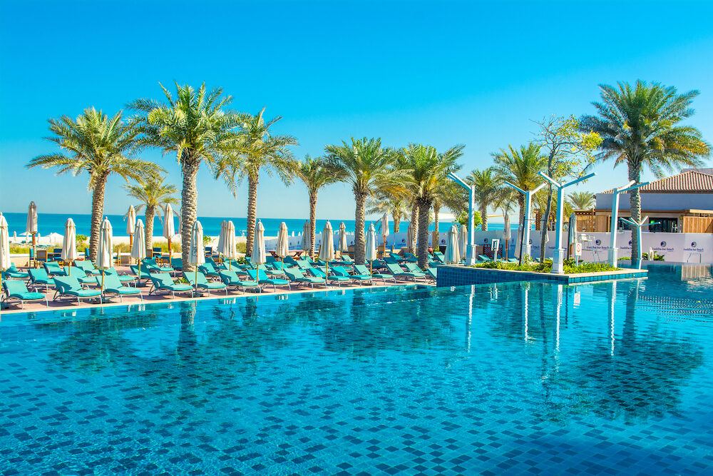 Adu Dhabi, UAE - Pool with blue water and sunbeds in the luxury hotel - St. Regis Saadiyat Island Resort