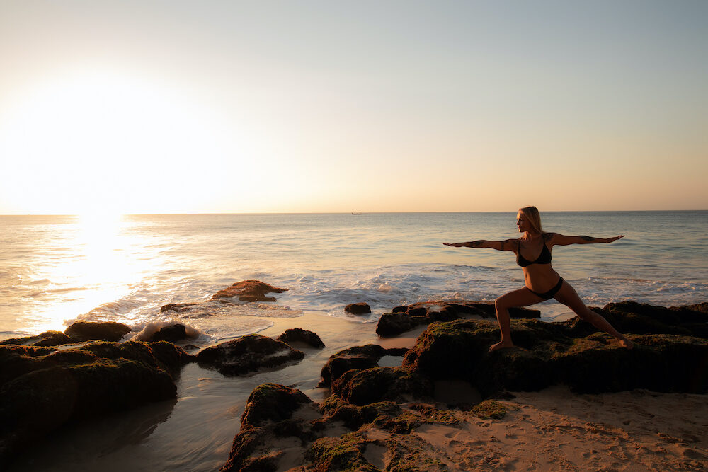 Yoga concept. Young woman practicing yoga, standing in Virabhadrasana pose on the beach. Silhouette of woman in Warrior pose. Sunset time. Yoga retreat, Bali. Copy space. Work out. Tegal Wangi beach