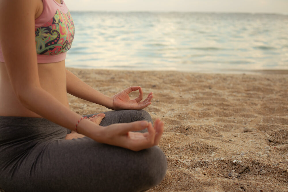 Lotus yoga pose. Close up. Focus on one hand. Yoga at the beach. Young woman sitting on sand, meditating, practicing yoga and pranayama with gyan mudra. Sunset time. Yoga lifestyle. Bali, Indonesia