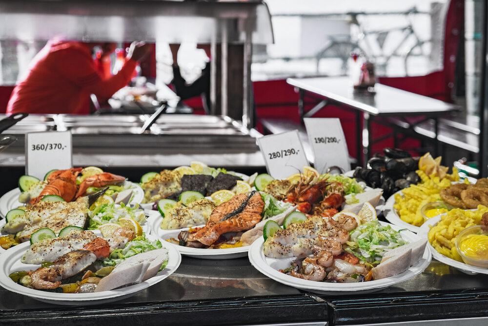 Delicious plates with a variety of grilled fish and seafood served with salad, french Fries and mayonnaise sauce. Street Food ready to eat with price tag at Bergen Fish Market, Norway