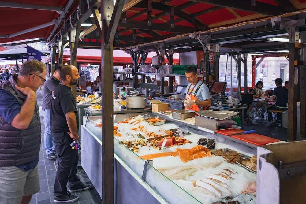 Bergen, Norway - People buy fish at the fresh seafood stalls in outdoor Fish Market in Bryggen - Hanseatic wharf, Bergen, Norway.