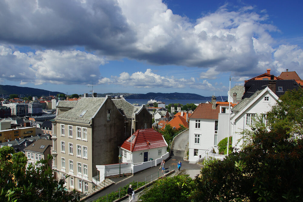 Travel to Norway, a street with tourists, going down between the houses in the city of Bergen