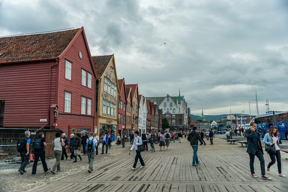 Bergen, Norway- photo of the wooden promenade of Bergen on a cloudy day. People walk along the waterfront