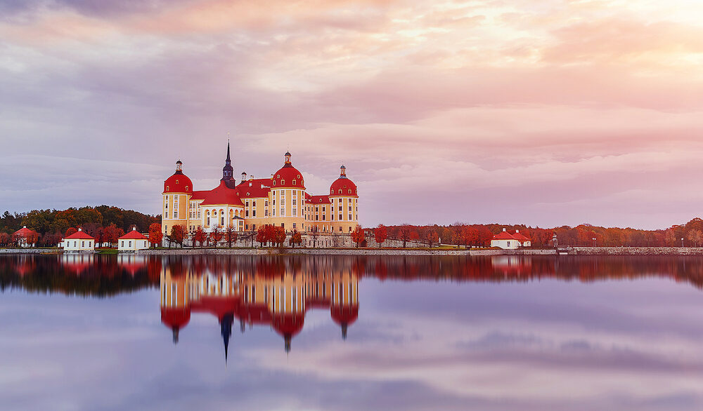 Splendid morning scene. Moritzburg Castle near Dresden with colorful sky during of sunrise, reflectad in water. Wonderful autumn scenery in Saxony, Dresden, Germany, Europe. Creative image