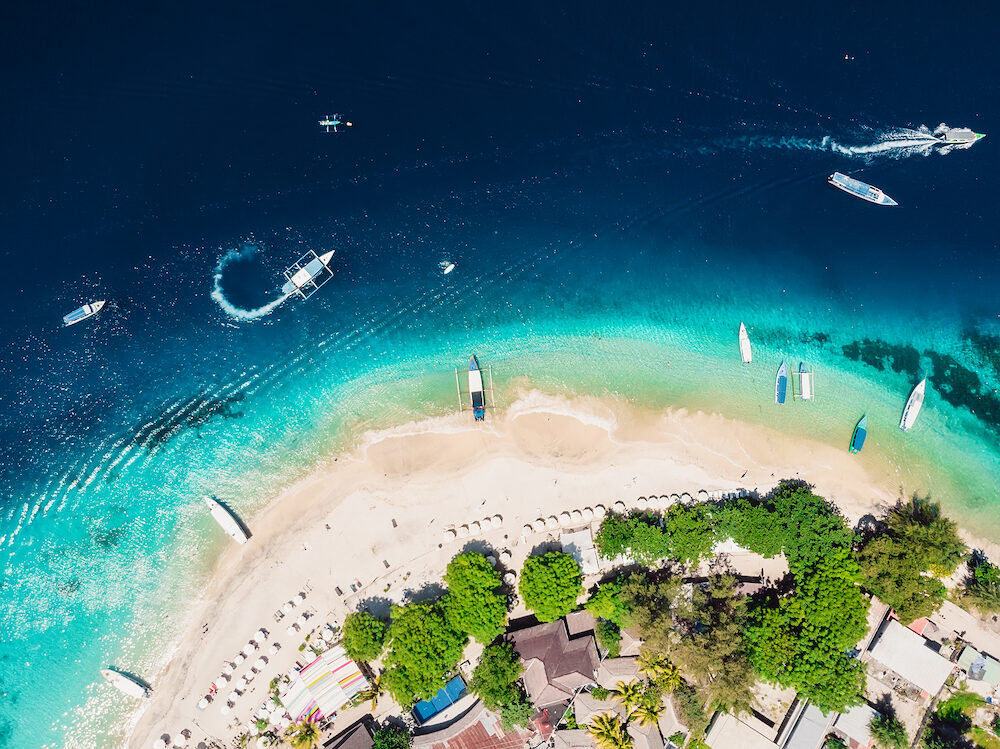 Tropical island with tropical beach and crystal ocean, aerial view. Gili islands
