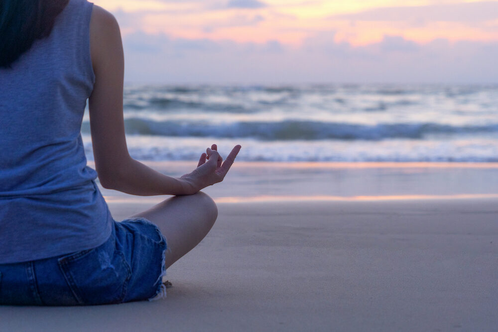 Happy Asian woman practicing yoga or exercising at the beach during travel holidays vacation outdoors at ocean or nature sea at sunset time, Phuket, Thailand