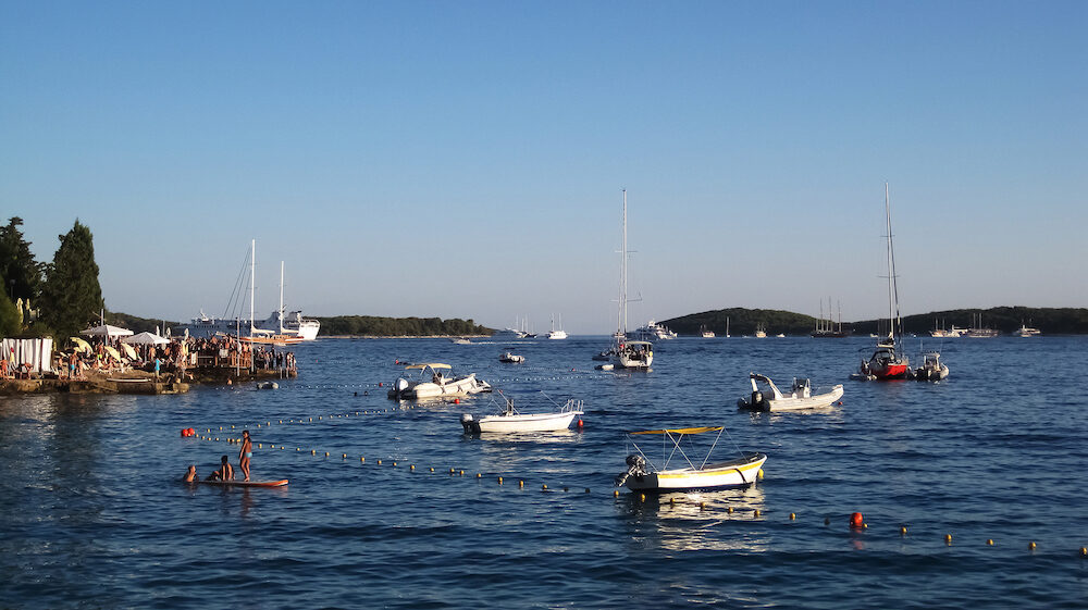 Hvar, Croatia - Young people having party on the beach club|bar in the bay at sunset