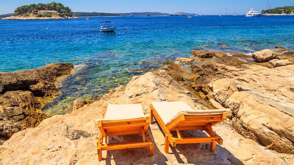 Coastal summer landscape - view of the beach loungers on a rocky seashore, on the island of Hvar, the Adriatic coast of Croatia