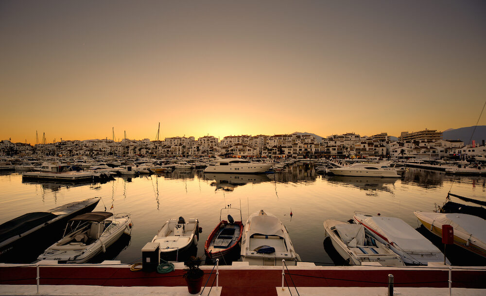 Luxury yachts and motor boats moored in Puerto Banus marina in Marbella, Spain. Marbella is a popular holiday destination located on the Costa del Sol in the southern Andalusia, it lies beneath the Cordillera Penibetica mountains