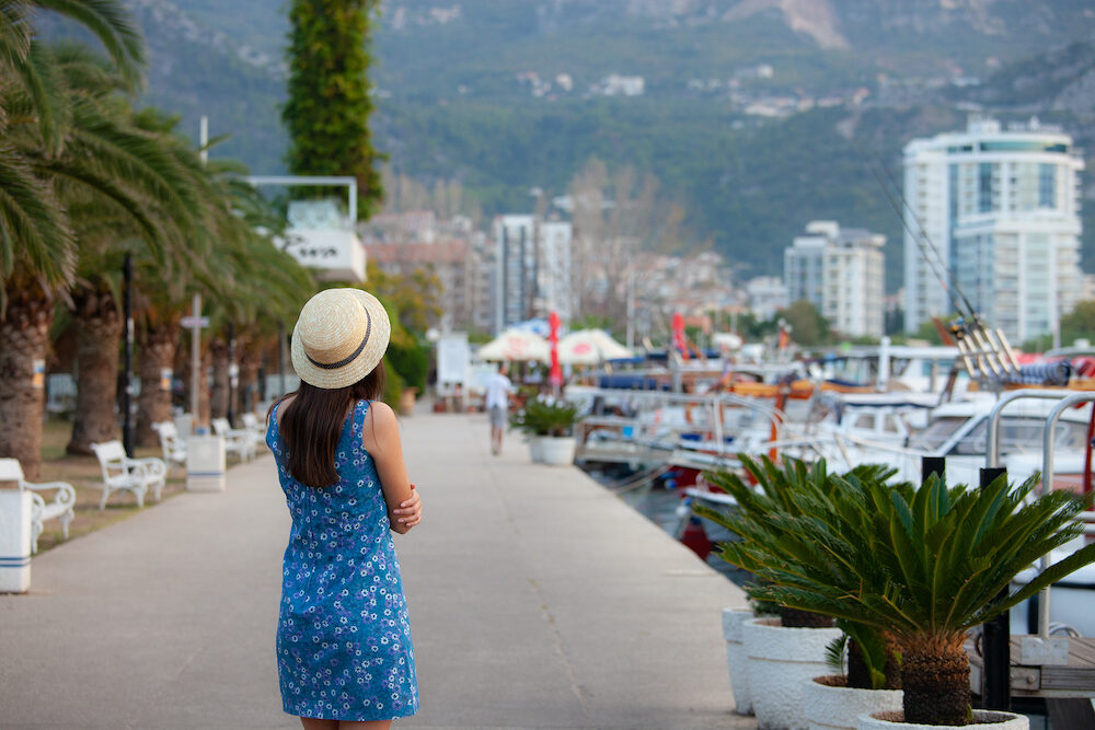 Europe summer travel mediterranean destination. Tourist woman on vacation, walking on the streets of old and beautiful Mediterranean city in hat and summer dress