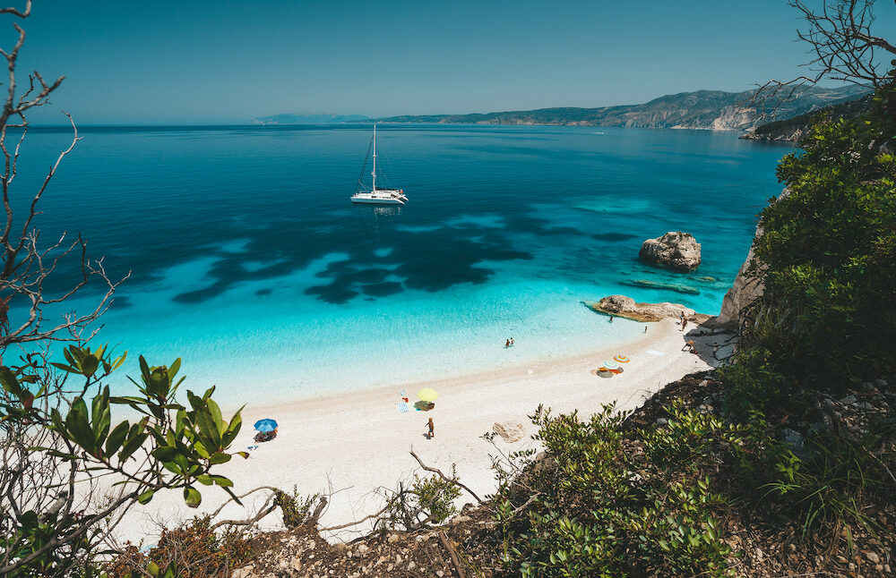 Fteri beach, Cephalonia Kefalonia, Greece. White catamaran yacht in clear blue sea water. Tourists on sandy beach near azure lagoon