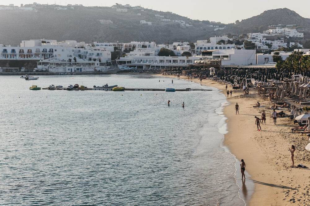 Mykonos, Greece - : High angle view of people the beach in Platis Gialos, a popular beach on the south coast of Mykonos, on a sunny day.