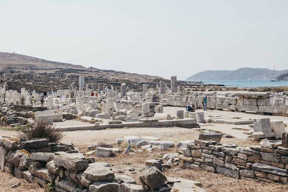 Delos, Greece - People walk by columns and ruins on the Sacred Way on the island of Delos, Greece, an archaeological site near Mykonos in the Aegean Sea Cyclades archipelago.