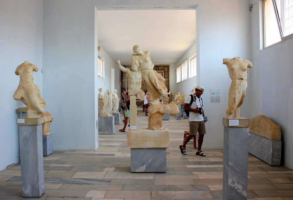 DELOS, GREECE - Tourists visit the Archaeological site, marble statues in the Museum