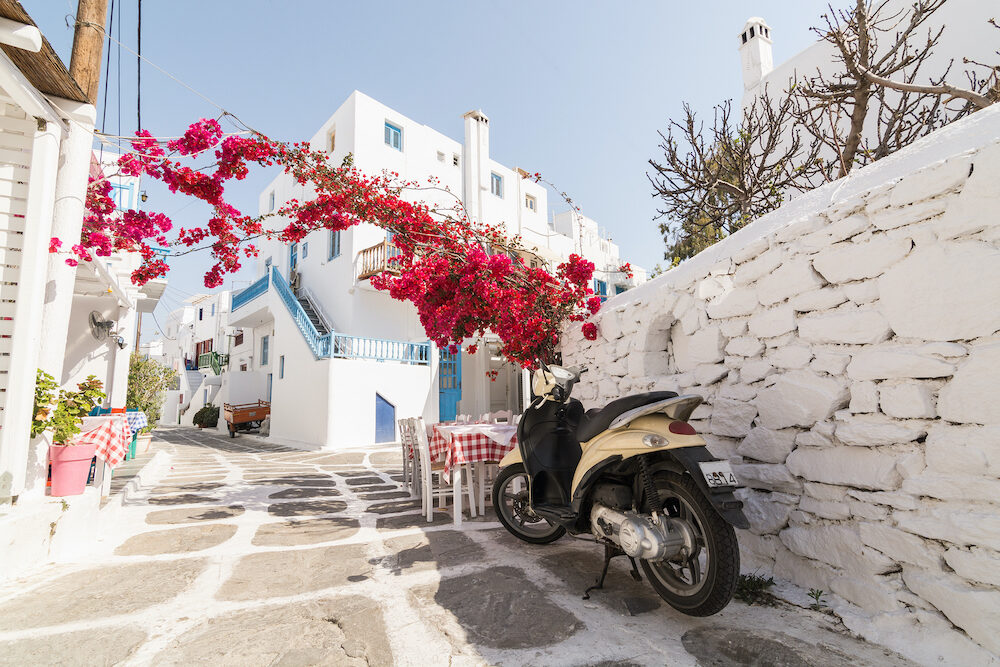 MYKONOS, GREECE - View over the old cobbled street in Mykonos town district Little Venice, restaurant and bush in blossom. Retro looking scooter on the foreground.