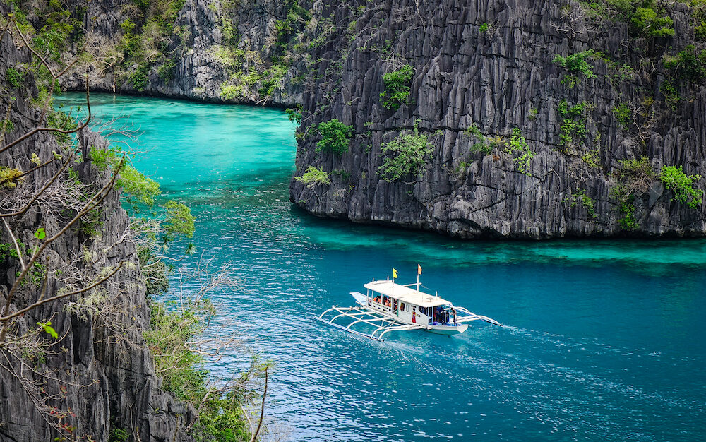 A traditional boat runs on Kayangan Lake in Coron Island Philippines. Coron has been described as one of the best spots in the World for Wreck diving.