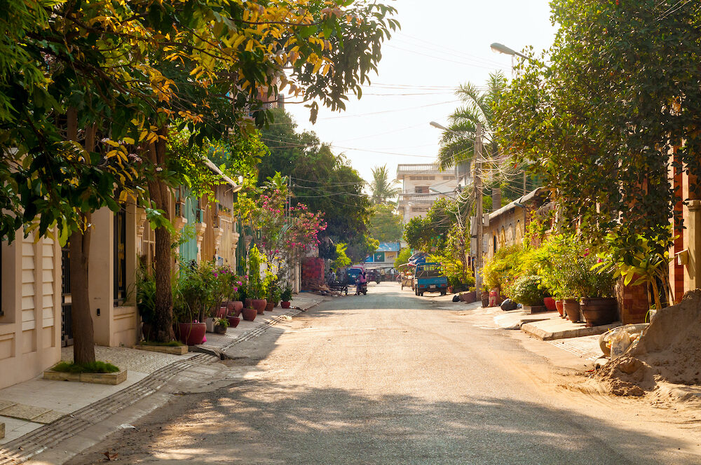 PHNOM PENH CAMBODIA - A quiet tree-lined street in Phnom Penh conceals residential spaces behind gated facades yielding to commercial activity at the far end.