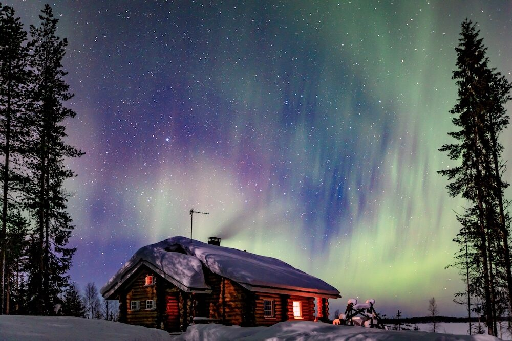 Polar arctic Northern lights Aurora Borealis activity over the wooden cabin in winter Finland, Lapland