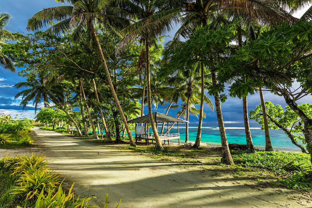 Tropical beach on Samoa Island with palm trees and dirt road, south of Upolu