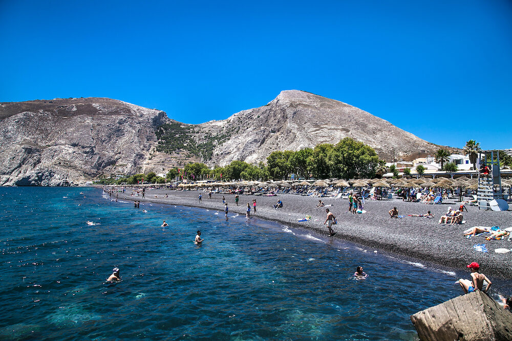 Santorini, Greece- People on Black beach of Kamari at Santorini island, Greece.