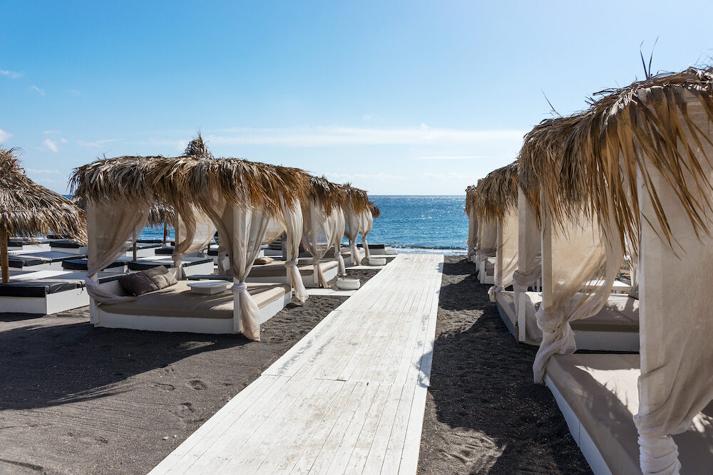 Relaxation zone on the beach between the villages of Perissa in Santorini