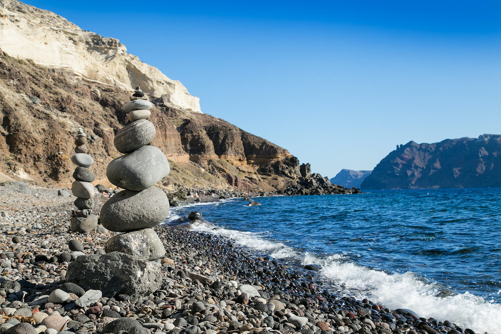 Stone pebbles stacked, ancient ritual for good fortune and prosperity at Black Katharos Beach on Santorini island, Greece.