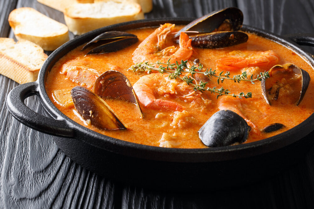 Seafood spicy soup with potatoes, shrimps, mussels, herbs and fish from a picad closeup in a pan served with toast. Horizontal top view from above