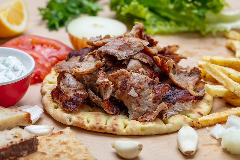 Shawarma, gyros on pita bread, vegetables and tzatziki sauce, top view. Traditional turkish, greek meat food.