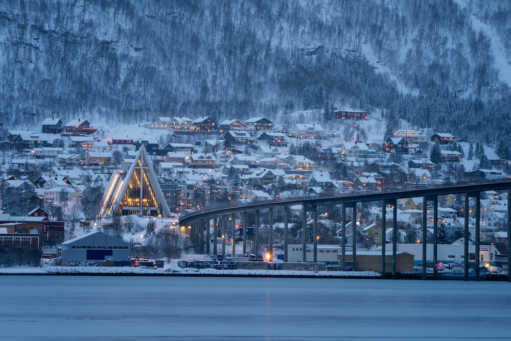 Arctic Cathedral with famous Tromso Bridge across Tromsoysundet strait in the background, Northern Norway