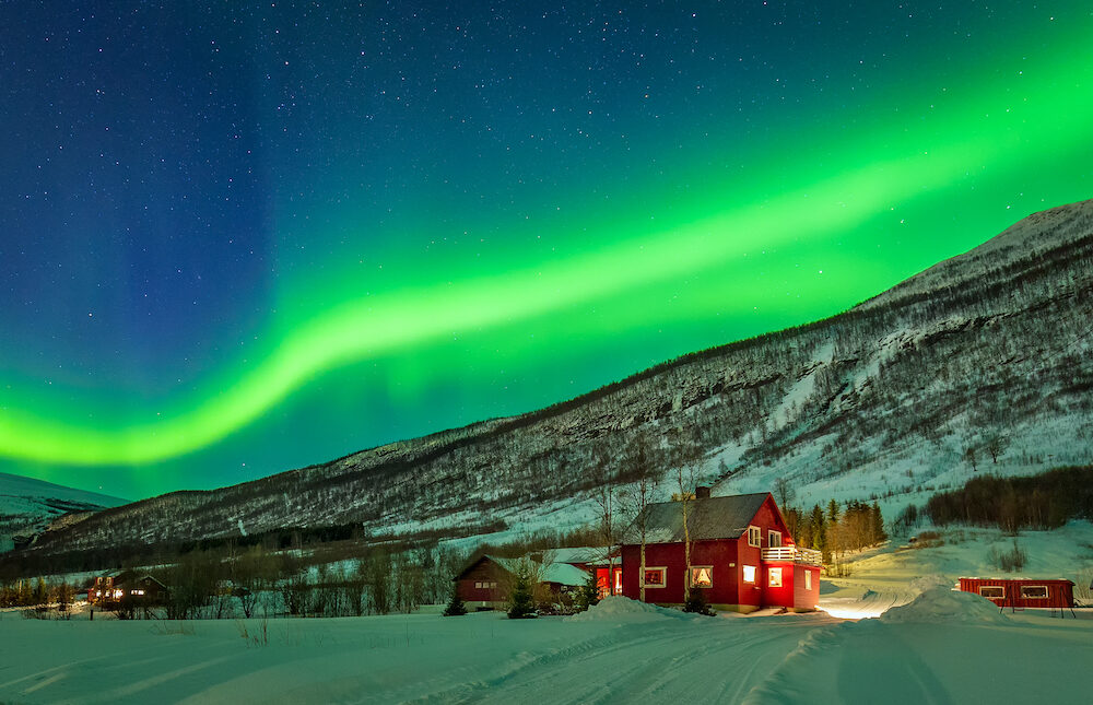 Aurora Borealis over mountain and rural house in distant Northern Norway. Green light of aurora lay over mountains.
