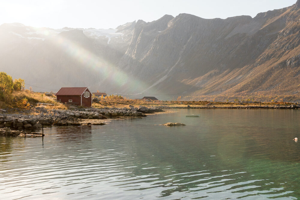 Beams of light with lens flare over a mountain peak shining down over a hut on the shoreline in Tromso, Norway on a misty day in a scenic rural landscape