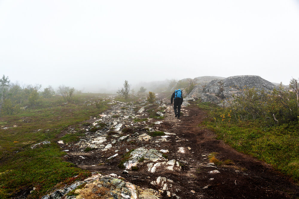 Lonely hiker on foggy mountain trail in Senja Norway