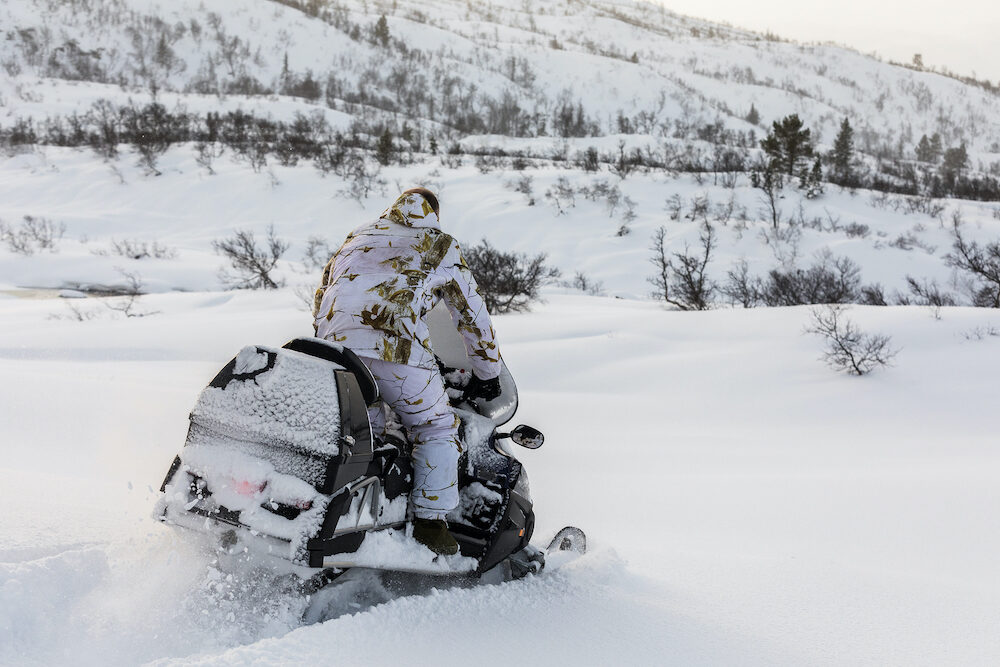 Man wearing winter camouflage clothing drives a snowmobile in the snow on the mountain in Norway