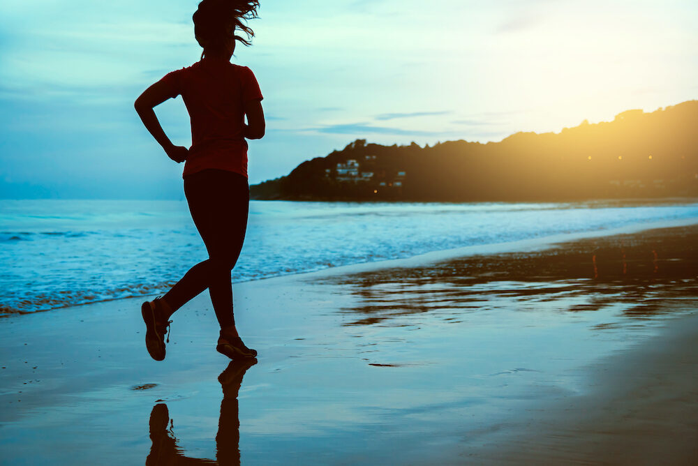 Asian women running workout jogging on the beach in the morning. extend the arms relax.
