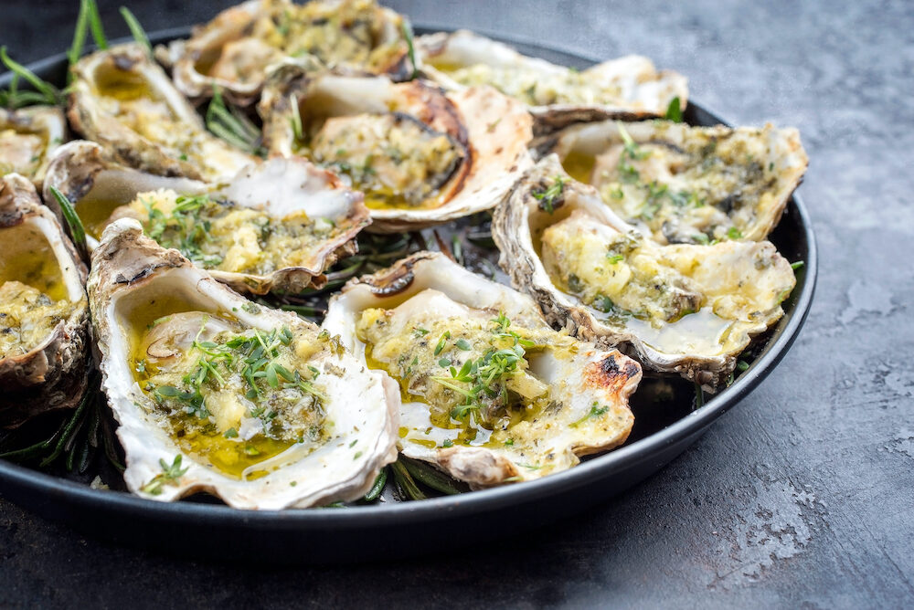 Barbecue overbaked fresh opened oyster with garlic and herbs offered as close up on a plate