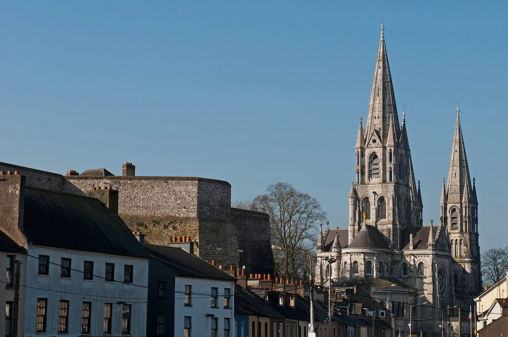 Cork cityscape featuring at the left Elizabeth Fort and on the right Saint Fin Barre's Cathedral Ireland (blue sky background)