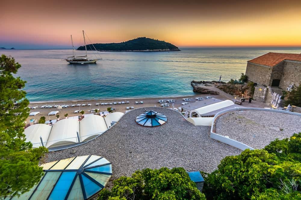 Sunset landscape over summer beach in Dubrovnik Riviera with island Lokrum in background , Croatia Mediterranean.