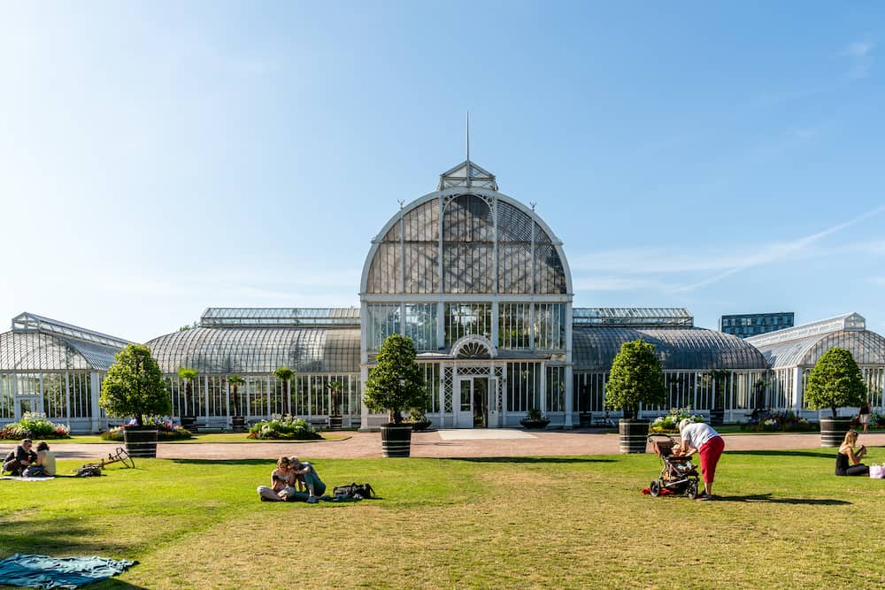 GOTHENBURG, SWEDEN Outdoor summer facade front view o a big beautiful glass greenhouse with incidental people in the foreground at the public Palm House, Garden Society in Gothenburg Sweden