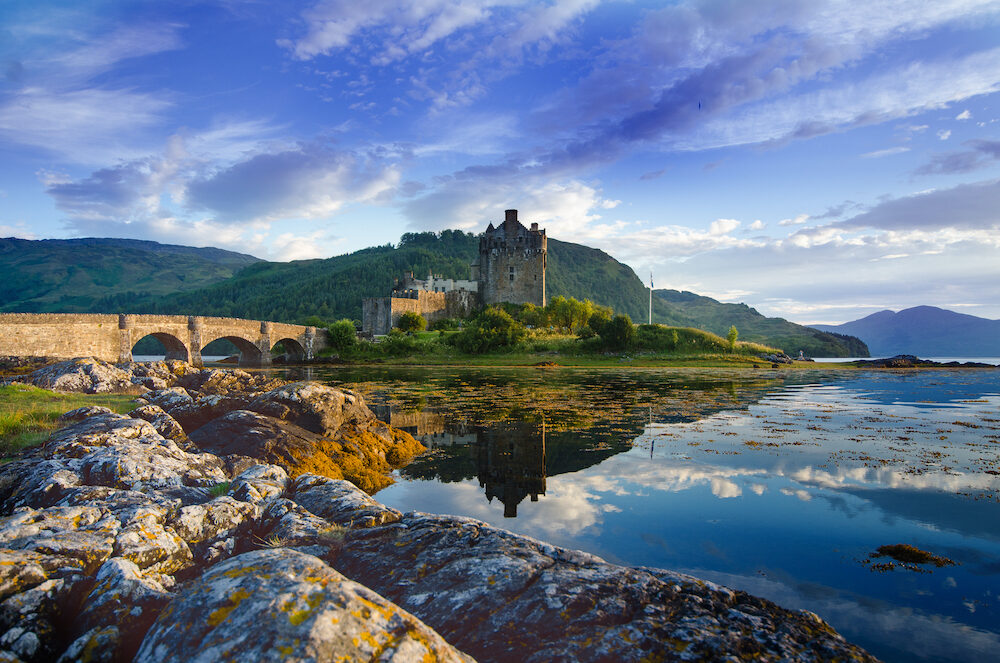 Tourists favourite place in Scotland - Isle of Skye. Very famous castle in Scotland called Eilean Donan castle. Scotland green nature. Top of the mountains. Beautiful nature. Scottish Highlands. Castle with reflection in the lake.