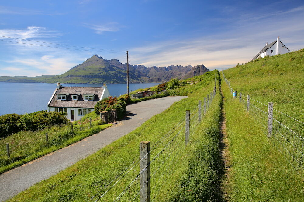 ISLE OF SKYE, UK - View of the Black Cuillin mountain range across Loch Scavaig from the coastal path near Elgol with traditional houses in the foreground