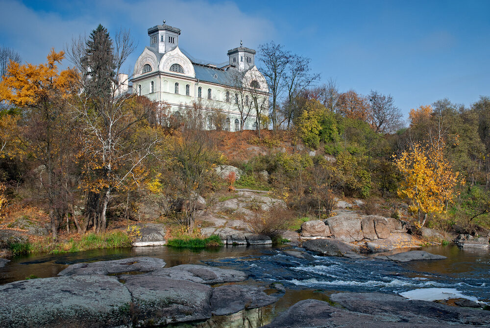 Beautiful old estate in autumnal trees with stream of water flowing below in Korsun-Shevchenkivskyi, Cherkasy region, Ukraine. Horizontal outdoors shot.