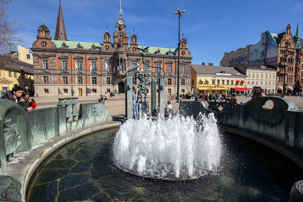 Malmo, Sweden - People watching at a fountain on the town hall square Stortorget.