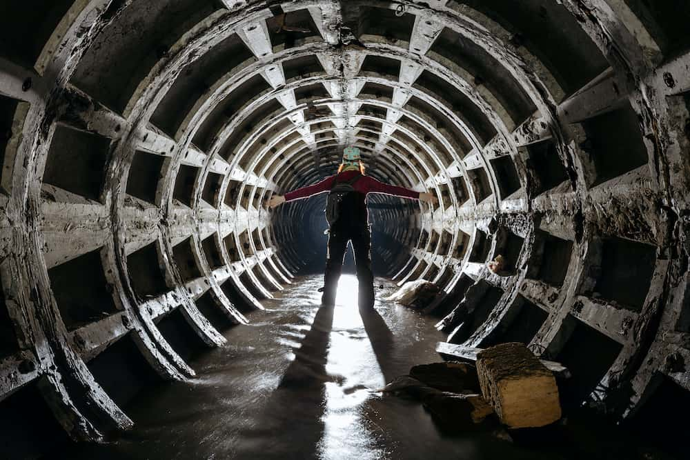 Silhouette of a man in the middle of the tunnel of the tubing in the dungeons of the city.