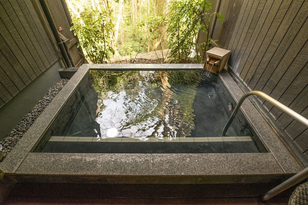 A Japanese Outdoor Onsen or Hot Tub in a forest for Nude bathing