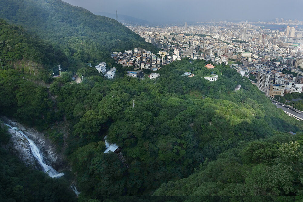 Birdeye view of Kobe cityscape, mountain,forest and Nunobiki waterfall from ropewape to mount Rokko in Kobe,Hyogo,Japan. Selective focus.